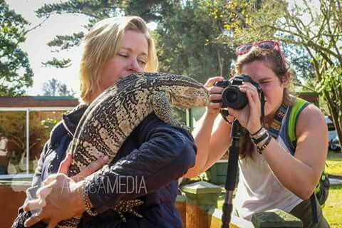 Our environmental journalism and travel writing interns cuddle up to a monitor lizard during their latest assignment.