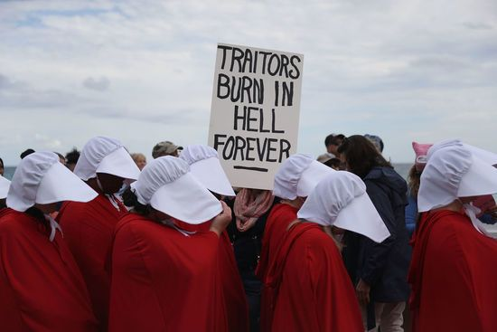 PALM BEACH, FL - JANUARY 20: People dressed as handmaidens protest against President Donald Trump on the one year anniversary of his inauguration on January 20, 2018 in Palm Beach, Florida. The  protesters marched to a checkpoint near President Donald Trump's Mar-a-Lago estate as they joined  thousands of people around the United States on the anniversary of TrumpÕs inauguration to state their  opposition to him and his policies. (Photo by Joe Raedle/Getty Images). The Deplorables Ball To…