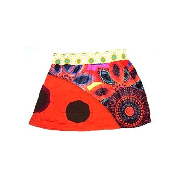 Mini falda de punto de algodón elástico  estampada con mandala de colores y parte de tejido liso con parches de tela en forma de círculo cosidos. Fajín elástico estampado. Mini falda muy colorida y original.