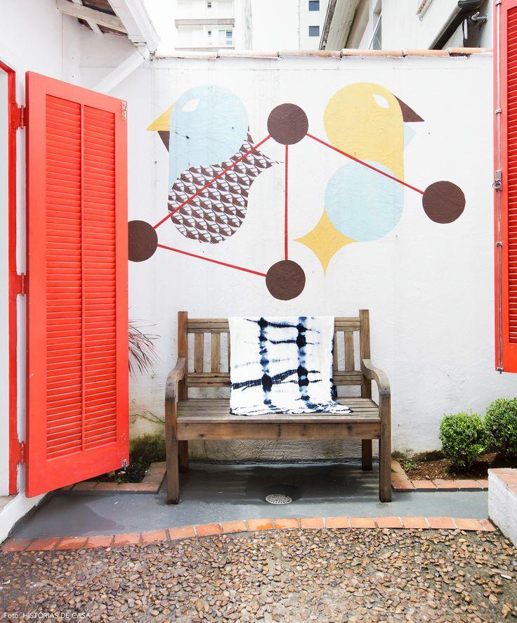 Quintal de casa de vila recebeu piso de pedrinhas e portas pintadas de vermelho. Para completar, o ambiente um grafite foi feito em uma das paredes.