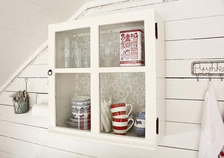 Vitriinikaapissa tavarat ovat näkösällä mutta suojassa pölyltä. Katso Meidän Mökin ohjeet ja tee oma kaappisi vanhasta ikkunasta!