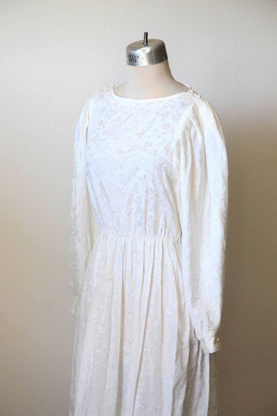 """A beautiful handmade wedding dress. In a retro 80s style, this dress has long poofy sleeves that button at the cuff. Dress has a floral printed design, and is an off-white ivory color. Not stark white. Waistband has elastic and fits snug at the waistline. The dress has belt loops but does not come with a belt. Dress is in great condition. ♫ SIZING Please double check measurements before purchasing. Shoulders: 14"""" Bust: 34"""" Waist: 28"""" Hips: 40"""" Length: 44"""" Sleeve Length: 25""""   ♫ DELIVERY…"""