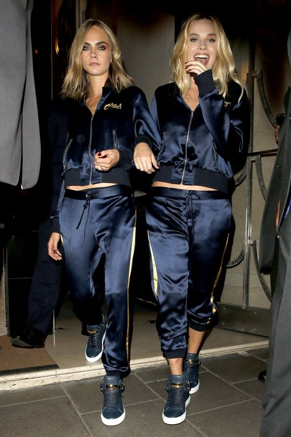 Cara Delevingne and Margot Robbie wearing track suits and trainers from Buscemi.