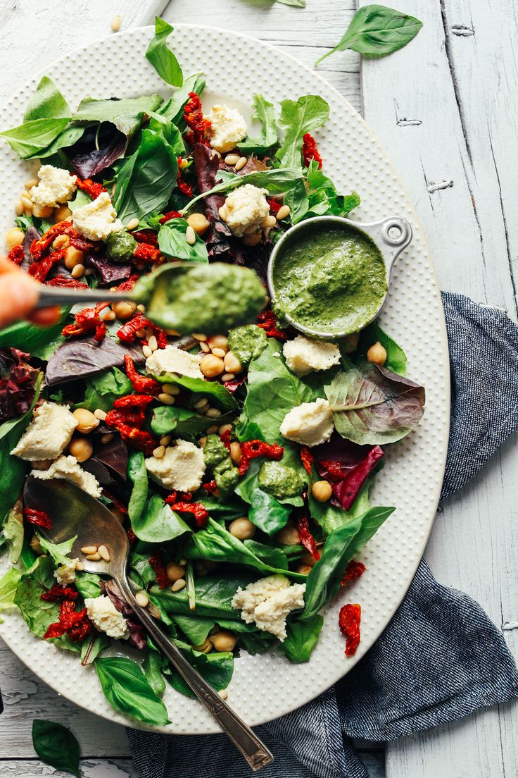 Quick-and-easy salad with mixed greens, almond ricotta, sun-dried tomatoes, pine nuts, chickpeas, and pesto dressing! A 30-minute plant-based meal!