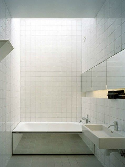 Bathroom ~ long mirror cabinet + ledge, overall white square tiles + same size gray on floor, tub front mirrored to visually expand the space designed by Claesson Koivisto Rune Design (for minimal 150-square-meter No. 5 House )