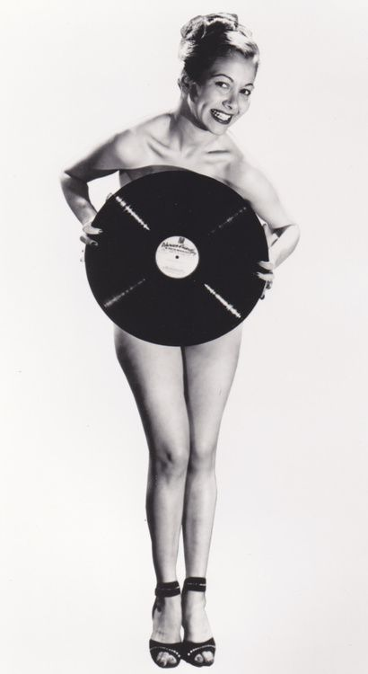 VICTORY GIRL, The Indelible Monica Lewis, posing with a Victory Disc, 1945.  © Monica Lewis Collection. S)