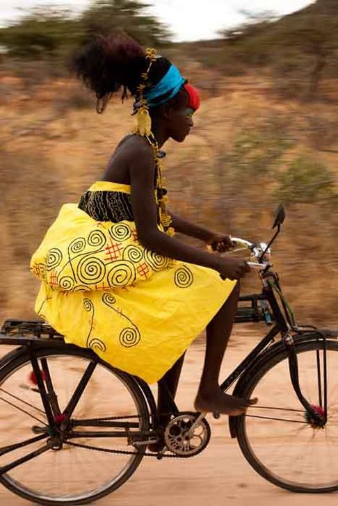 Fantastically multicoloured cyclist in a bright yellow dress with a red fringe and a blue hair wrap...