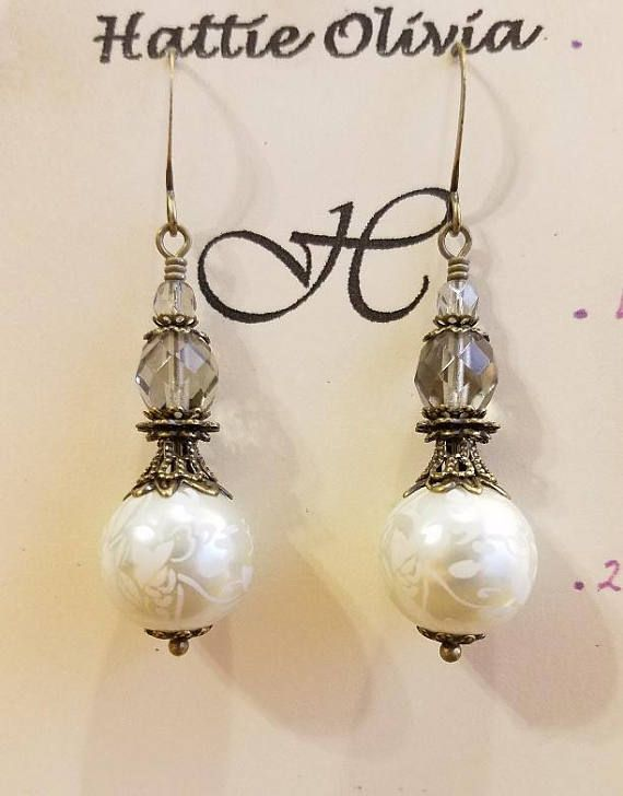 A beautifully scrolled 12mm pearl, dressed in layers of bronze filigree, is topped with either a copper luster czech pair of graduated beads or smokey quartz beads. These pearls are absolutely gorgeous, and are my favorite. I used 8 layers of bronze filigree pieces for each