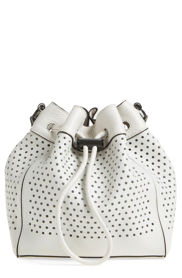 Perforations detail this leather bucket bag featuring an interior zip pouch perfect for stowing smaller items, while black hardware enhances the sophisticated look of this compact style.