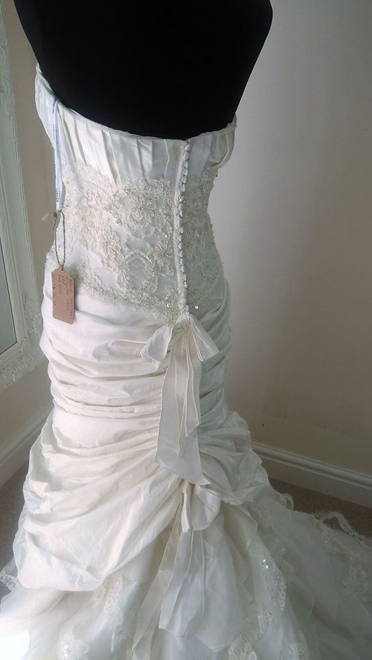 This beautiful Ian Stuart Nelle wedding dress has a pleated silk bust with a stunning embellished lace bodice.  The zip and button back fastening has two bows going across the middle and at the top of the chapel length train.  The elegant silk ruched fishtail skirt has a exquisite lace hem going all the way around and also a layer in the centre of the train.  Size 10  New and unworn without tags... See more — at Petersfield Town.