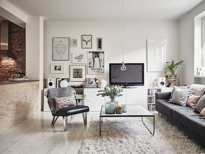 Vardagsrum avdelat med bänk klädd i plywood, soffa, matta, tv, soffbord, fåtölj, tavelvägg