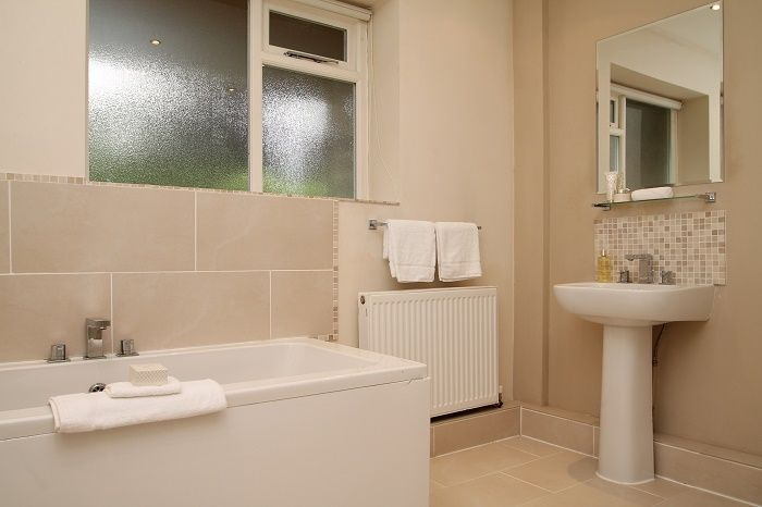 Bathroom staged with rental towels and accessories.