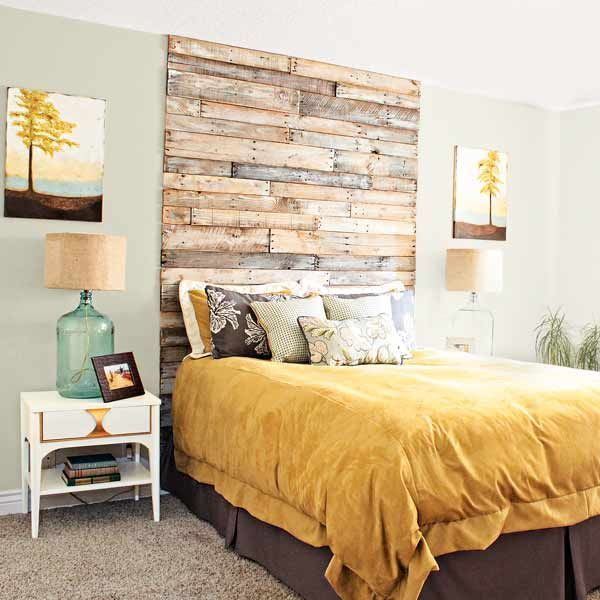 A DIY floor-to-ceiling headboard made of salvaged pallet boards gives this bedroom a loftier feel. | thisoldhouse.com