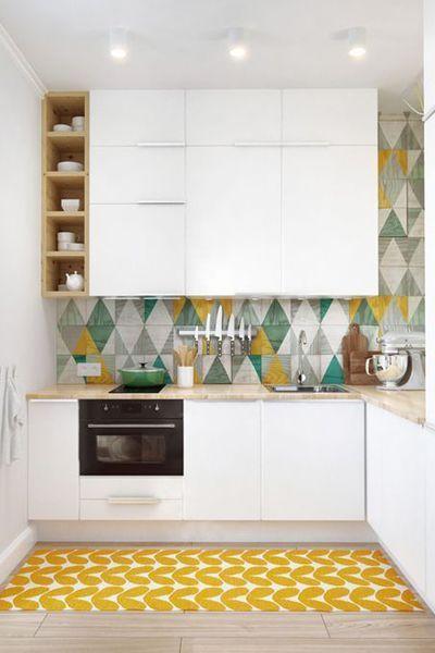 Hoge keukenkastjes en een kleurrijke tegelwand. Tof!