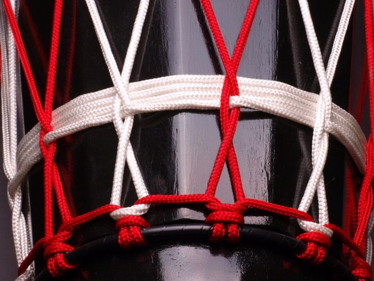 Ashiko hand drum close up, red and white polyester rope.