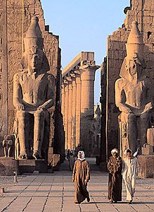 The outer court of the Temple of Luxor in Thebes, Egypt, with giant statues of King Ramses II.
