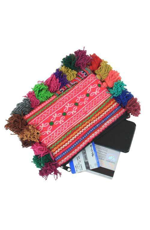 An adorable little pink hill tribe offbeat coin purse clutch with colorful pom pom hairs