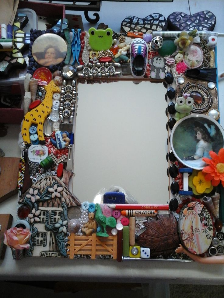 A mirror framed with lots of bits n pieces from around the house.