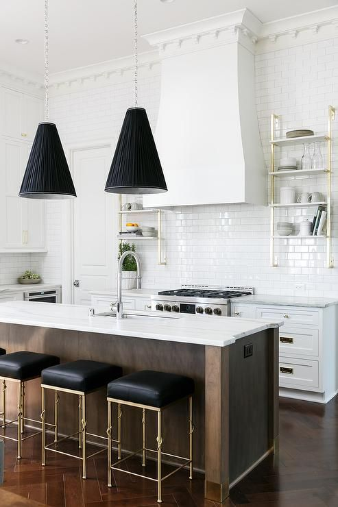 Accented with white dentil moldings, white subway backsplash tiles hold a white range hood between gold and marble French wall mount shelves.