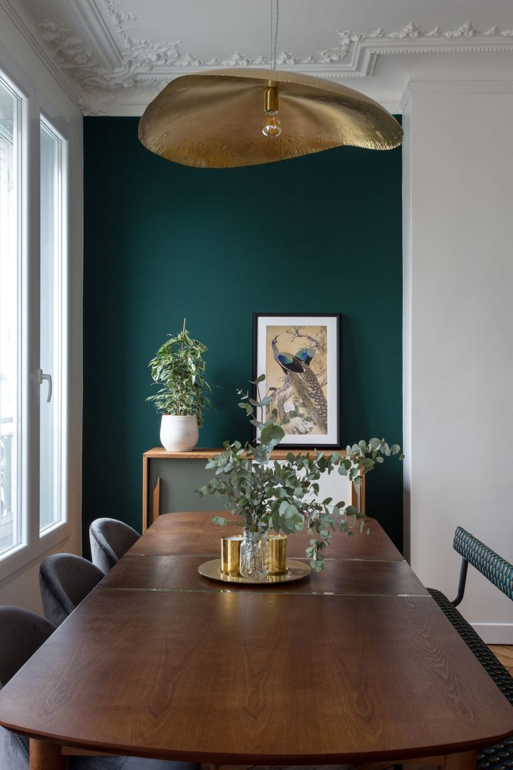 a vintage touch in this Parisian dining room green wall and brass details