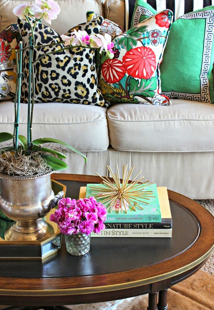 Do you own a white or beige couch? Glam it up with tropical or palm print decor and furniture pieces. EASY and WON'T break the bank! tropical print pillows decor eclectic spring 2016 design trends oval coffee table plants faux leopard pillow grey neutral couch ideas design how to decorate house