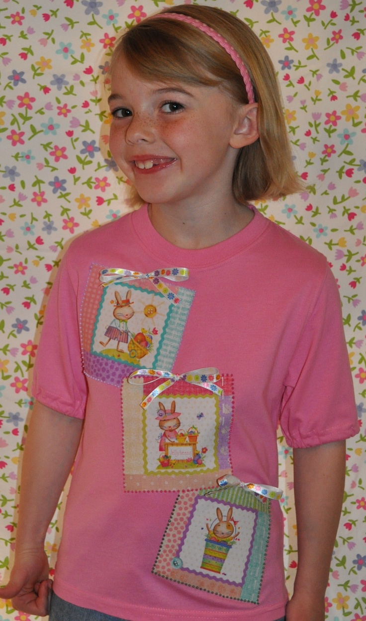 Easter/Springtime Toddler/Girl Jelly Beans Bunnies Shirt, Colorful With Decorative Ribbon Bows.  This cute and decorative spring shirt is for toddler girls & older girls. Variety of images of bunnies on fabric is bonded to a pink shirt, & colorful fabric paint outlines each bunny scene. Decorative ribbon bows are firmly sewn to the top of each bunny scene.  Available in many sizes.  Short/long sleeve available…