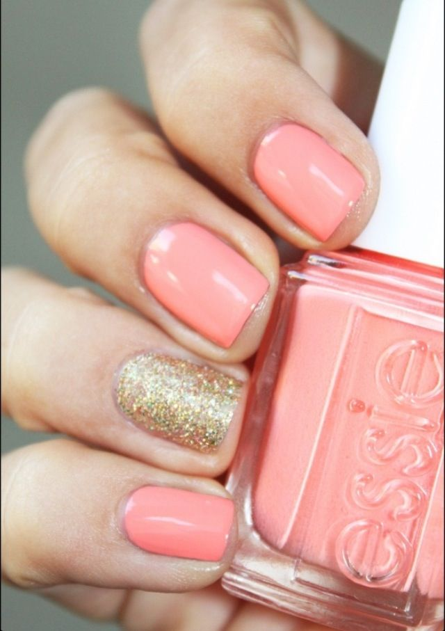 coral nails with a gold statement finger