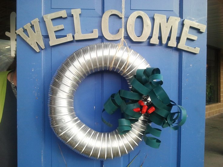 Upcycled Holiday or Christmas wreath.  Made with duct work, green venetian blinds, and red wire nuts.   Materials found at the Lexington, KY Habitat for Humanity ReStore