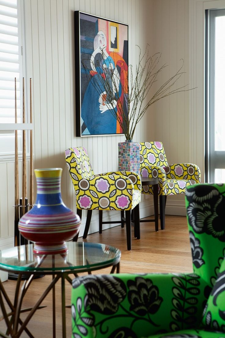 Billiard room featuring brightly upholstered armchairs, artwork and accessories.