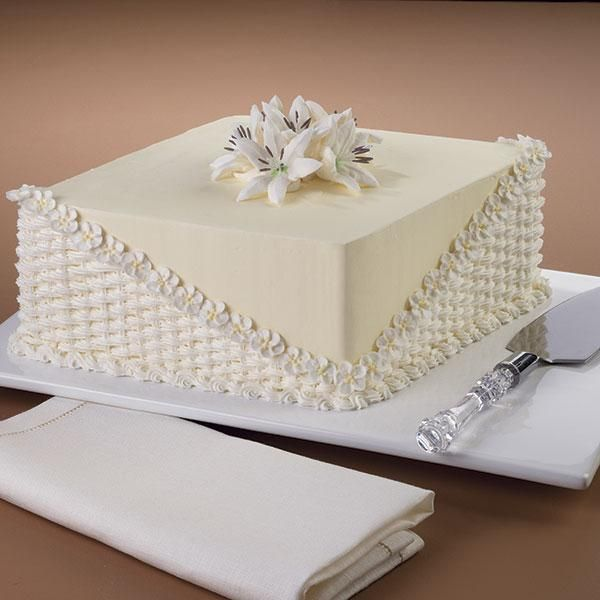 Lily Fair Cake - With this cake, springtime lasts all year long! A bouquet of exquisite lilies is framed by basketweave and an apple blossom border on a design that features techniques from our Flowers and Cake Design Course.