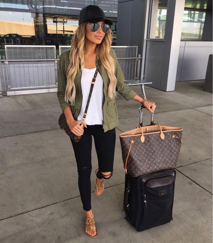 Military utility jacket, worn jeans, white tee and sandals for airport outfit