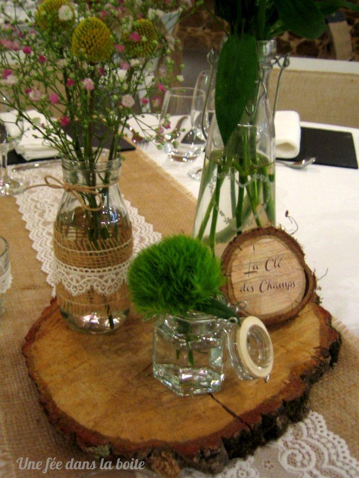 """Mariage """"Campagne-chic""""  Gros plan sur le centre de table composéde 3 jolis flacons de verre sur rondin de bois Un mini rondin présente le nom de la table"""