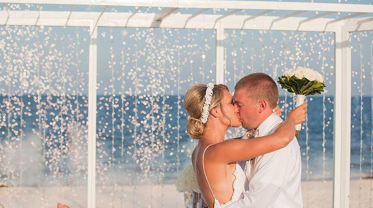Sea glass beaded curtain makes a magical backdrop at the beach altar | Palace Resorts Weddings ® #destinationwedding
