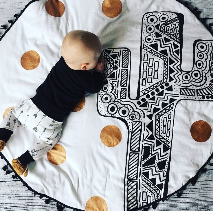 Our 'Cactus' playmat is approx 1m in diameter and made from handpainted cotton drill, with a black cotton poplin backing. It is padded for babies comfort and is edged with black fringe trim. It features a black Cactus with copper metallic spots.Water based inks are used and our mats can be washed on the gentle cycle in the washing machine. These are made to order with a 2-4 week turnaround. #nursery #baby #playmat