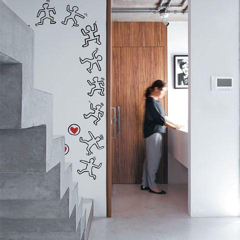 Casa 2. Chumbada à parede, a escada de alvenaria também se conecta à viga do teto. São do artista gráfco americano Keith Haring os adesivos trazidos de uma viagem à Áustria. A cuba de Corian fca fora do lavabo, cuja porta exibe acabamento de laminado no padrão amêndola.