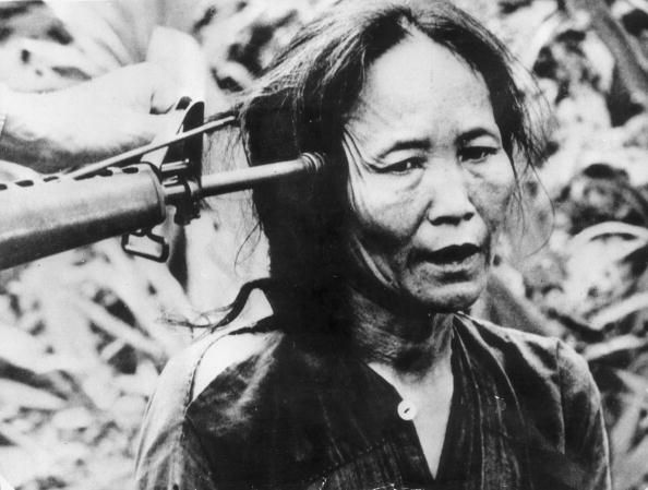 A Vietnamese civilian with a gun pointed at the side of her head. - My Lai Massacre