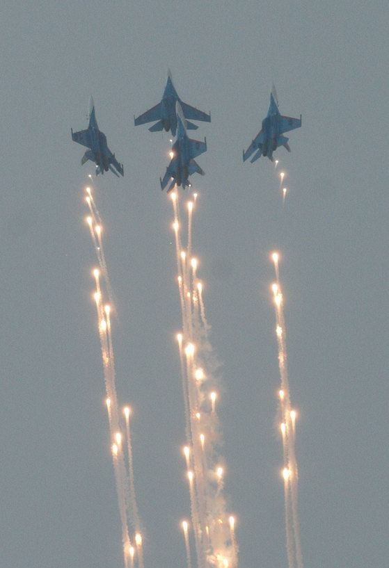 Russian Knights celebrating the Russian Air Force 100th anniversary with a perfect, flare-riveted dance in the sky, riding their Sukhoi Su-27s fighter jets.