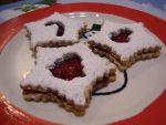 This Norwegian cookie has lingonberry jam sandwiched between two almond cookies with a cute cutout on the top that lets the red jam peak through. -By Carrie (Strommen) Lennie