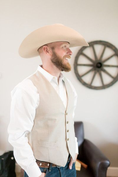 Rustic groom outfit idea - white button-down shirt, tan vests, dark denim pants and cowboy hat {Irving Photography}
