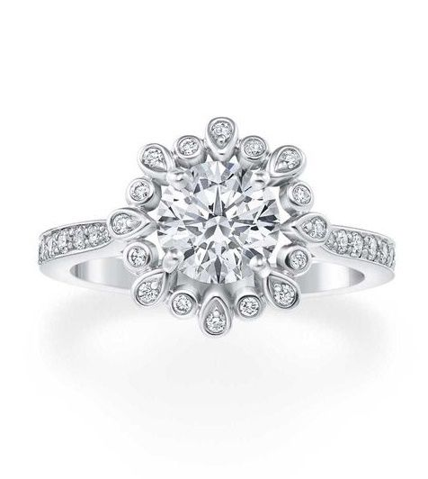 A halo of 16 diamond petals surround a round brilliant-cut diamond, available in three carat sizes, in the Blossom, the latest Harry Winston engagement ring, inspired by one of the jewellery house's perennial motifs.
