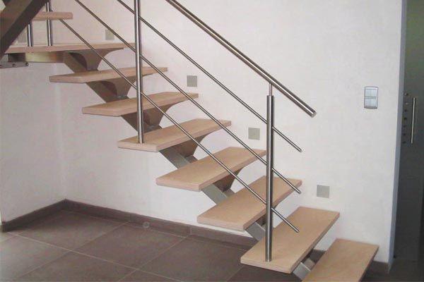 Escalera interior con zanca central, peldaños de madera y barandilla de acero inoxidable.