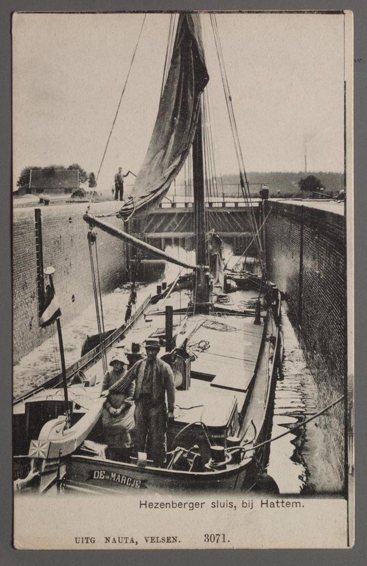 De klipperaak 'De vr Margje' vaart door de Hezenberger sluis bij Hattem. Linksachter een sluiswachter en op de voorgrond een man en een meisje in klederdracht.  1900-1910 #Veluwe #Gelderland #nieuwedracht