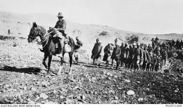 Beersheba, Palestine. c 1917. A large group of Turkish prisoners, being led by an Australian soldier of the Light Horse on horseback. Note the soldiers in the background (middle and left) taking a photograph of the Turkish prisoners as they are being led away. (Donor J. Mulholland) ...