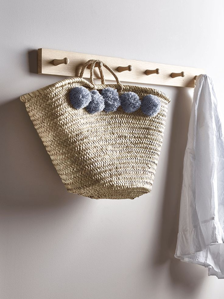 Beautifully hand woven from palm leaves by artisans in Morocco and finished with fun, light grey wool pom poms, our sweet market basket makes a lovely alternative to plastic shopping bags. Equally perfect for storing small essentials around the house, it is made from all natural materials.