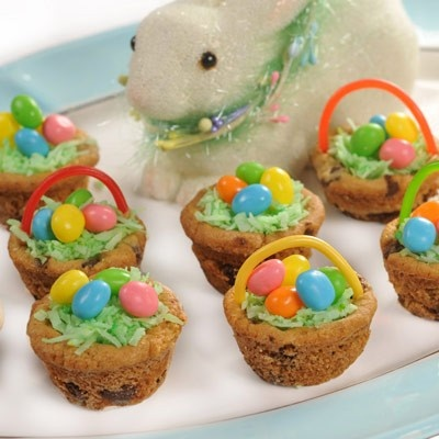 Chocolate Chip Easter Baskets     Ingredients   1 package (16.5 oz.) NESTL TOLL HOUSE Refrigerated Chocolate Chip Cookie Bar Dough  1 cup prepared white frosting  Green food coloring  1/4 cup sweetened flaked coconut  WONKA SweeTARTS or SPREE Jelly Beans  Thin-string licorice, various colors, cut into 3-inch pieces for basket handles   PREHEAT oven to 350 F. Grease and flour 24 mini-muffin cups. Place one square of cookie dough into each cup.