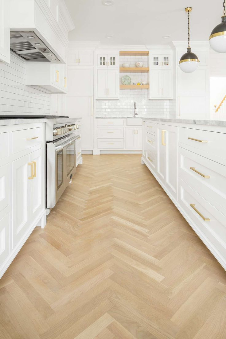 White oak wood floor in herringbone pattern in white kitchen. White English farmhouse style home by The Fox Group. Come be inspired these English Farmhouse Style Decorating Ideas. #modernfarmhouse #englishfarmhouse #interiordesignideas #farmhousestyle #decoratingideas #kitchendesign #whiteoak #herringbone