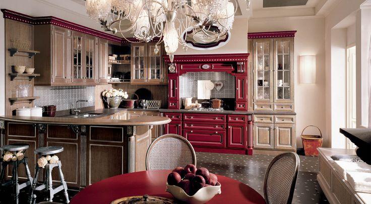 Cucina in castagno con elementi rossi, decori in argento, top e alzatine in quarzo.