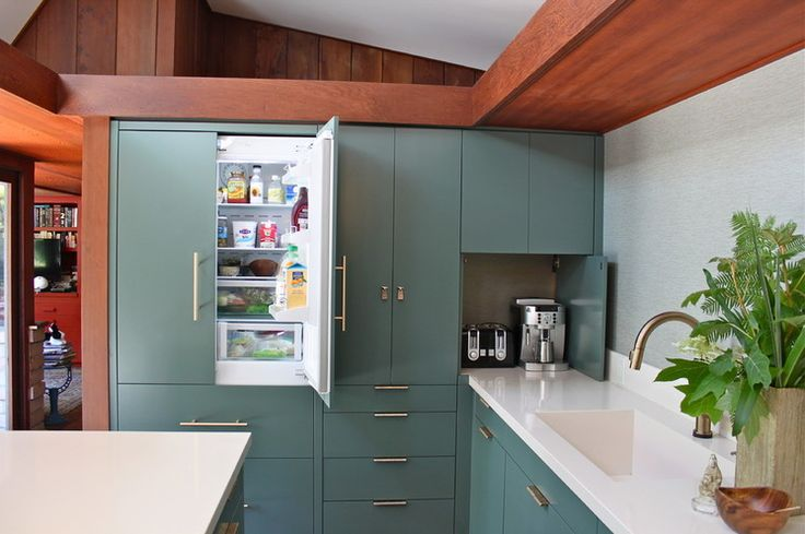 The cabinets are painted with a conversion solution that is sprayed on and resembles laminate when dry. Like the vinyl wallpaper, this paint can stand up to the usual kitchen abuse.   Cabinet paint: Caldwell Green, Benjamin Moore