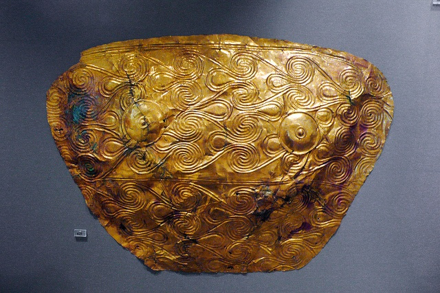 mycenae - breastplate    Shaft Grave V, Grave Circle A, Mycenae. 1600-1500 BC.  National Archaeological Museum, Athens.    Gold funerary breastplate decorated with repoussé spirals. Two repoussé circles indicate the nipples. The breast plates are reminiscent of the luxurious Pharaonic Egyptian burials, where the mummified bodies were covered entirely with gold.