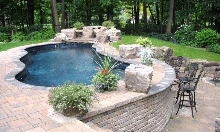 This Leisure Pool shown in Out back blue color with raised retaining wall and water features. The decking was done with cobble stone pavers.  (Pinning this for the retaining wall since our pool would be on a hill)